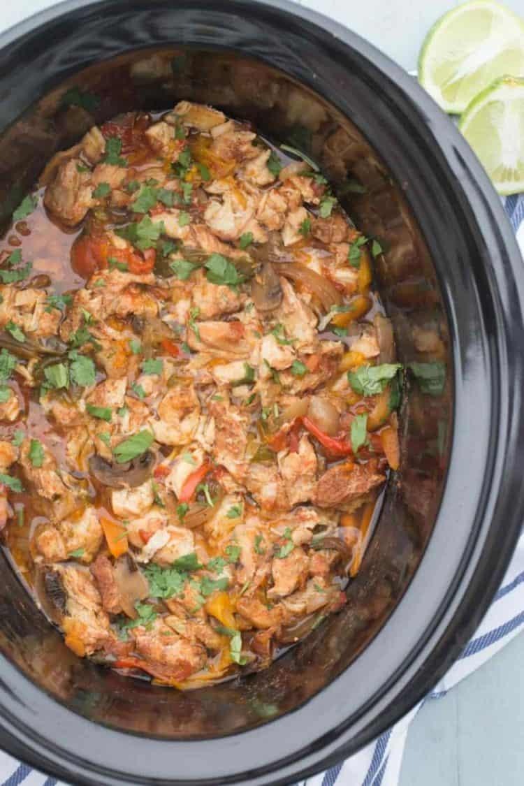 Crock pot chicken fajitas in a crock pot garnished with fresh herbs.