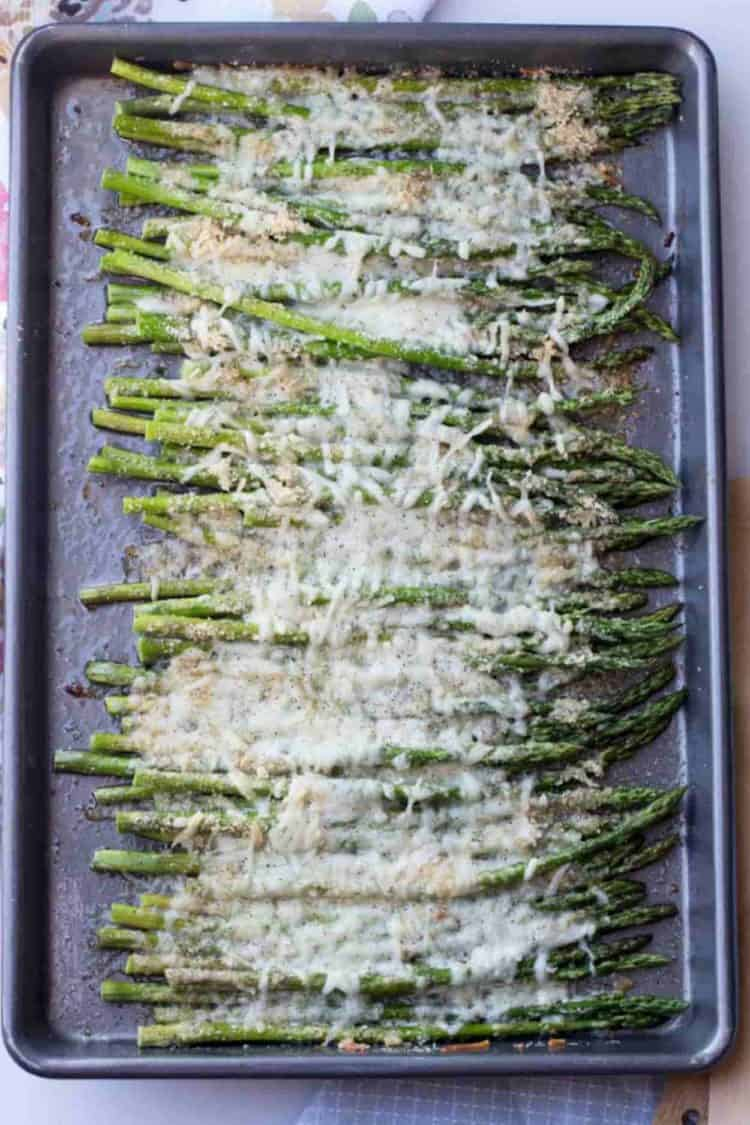 Cheesy baked asparagus in a baking sheet topped with cheese and fresh grated black pepper.