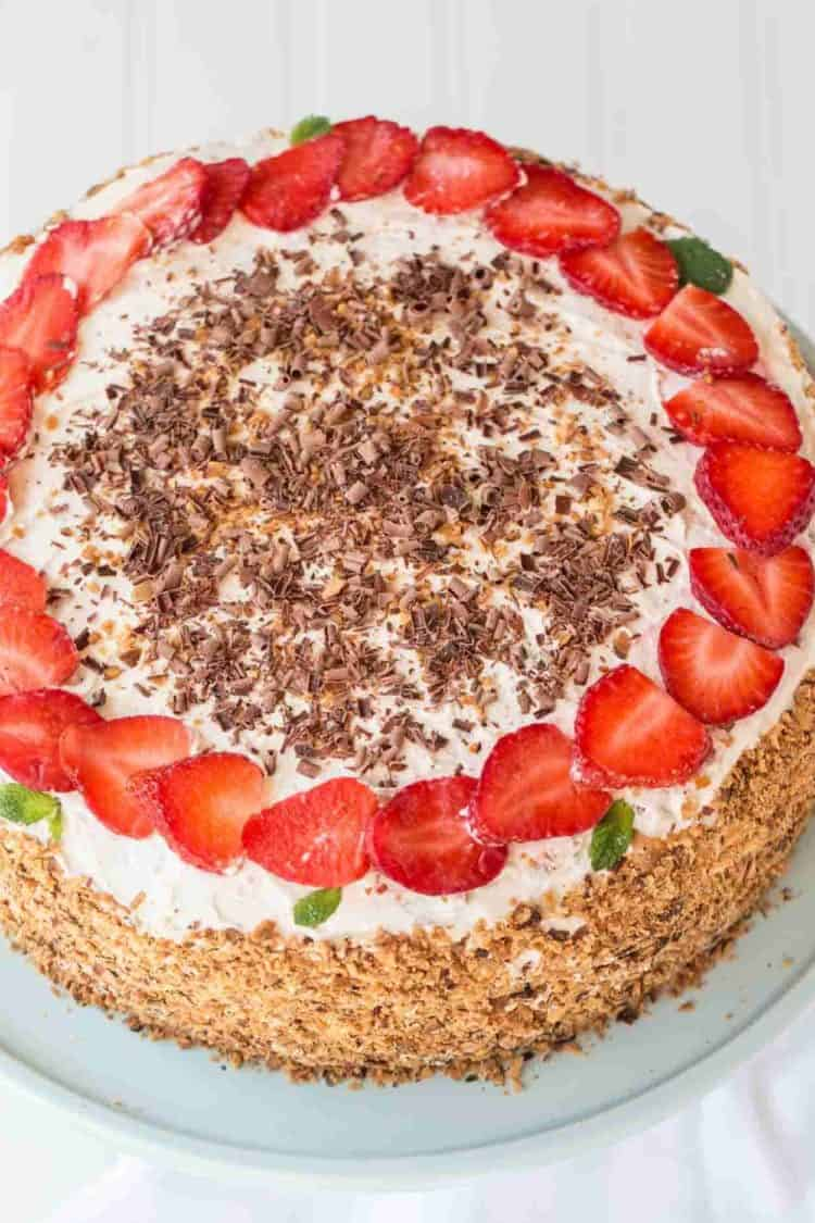 Strawberry cake topped with strawberries, toasted coconut shavings and chocolate strawberries.