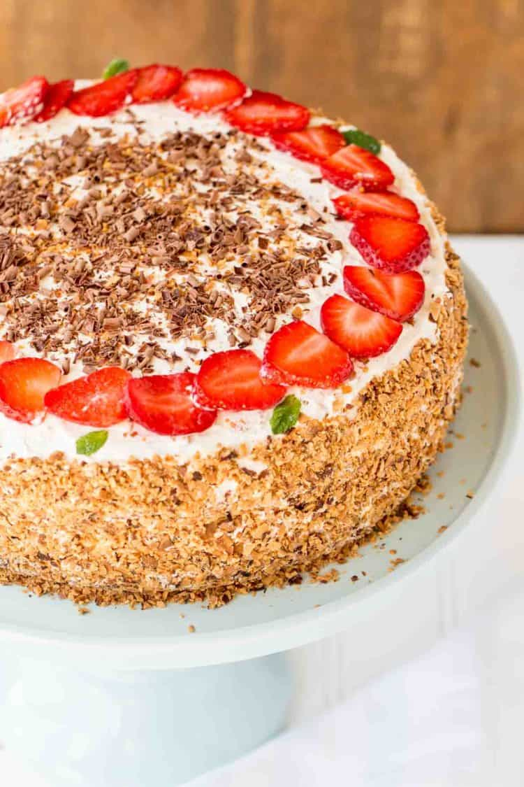 Layered cake with chocolate cake and strawberries on a cake platter, topped with strawberries and toasted coconut.