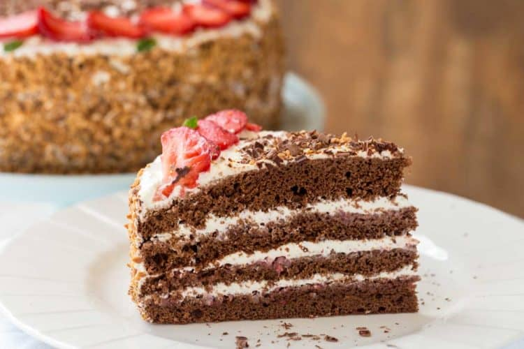 Layered chocolate strawberry cake slice with a sweet cream frosting and a strawberry puree layer.