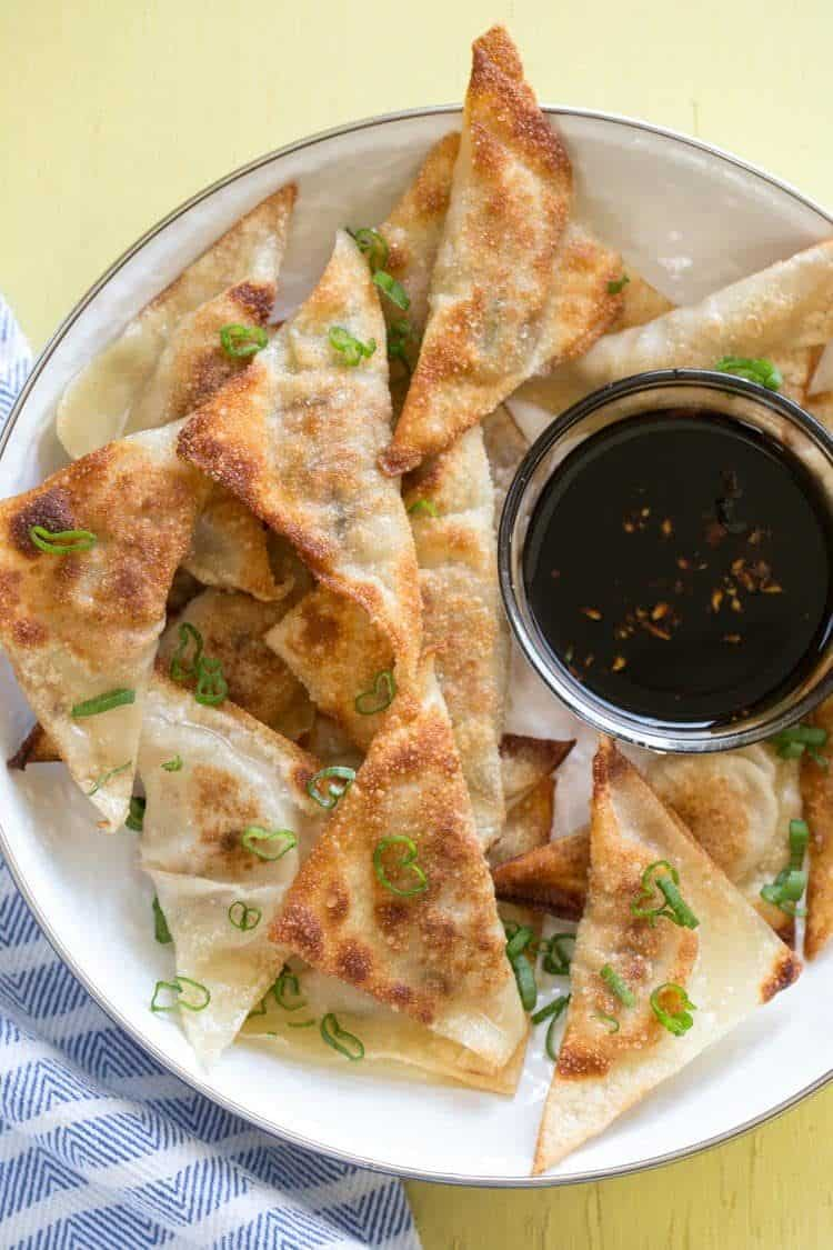 Stacked pot stickers in a bowl with dipping sauce.