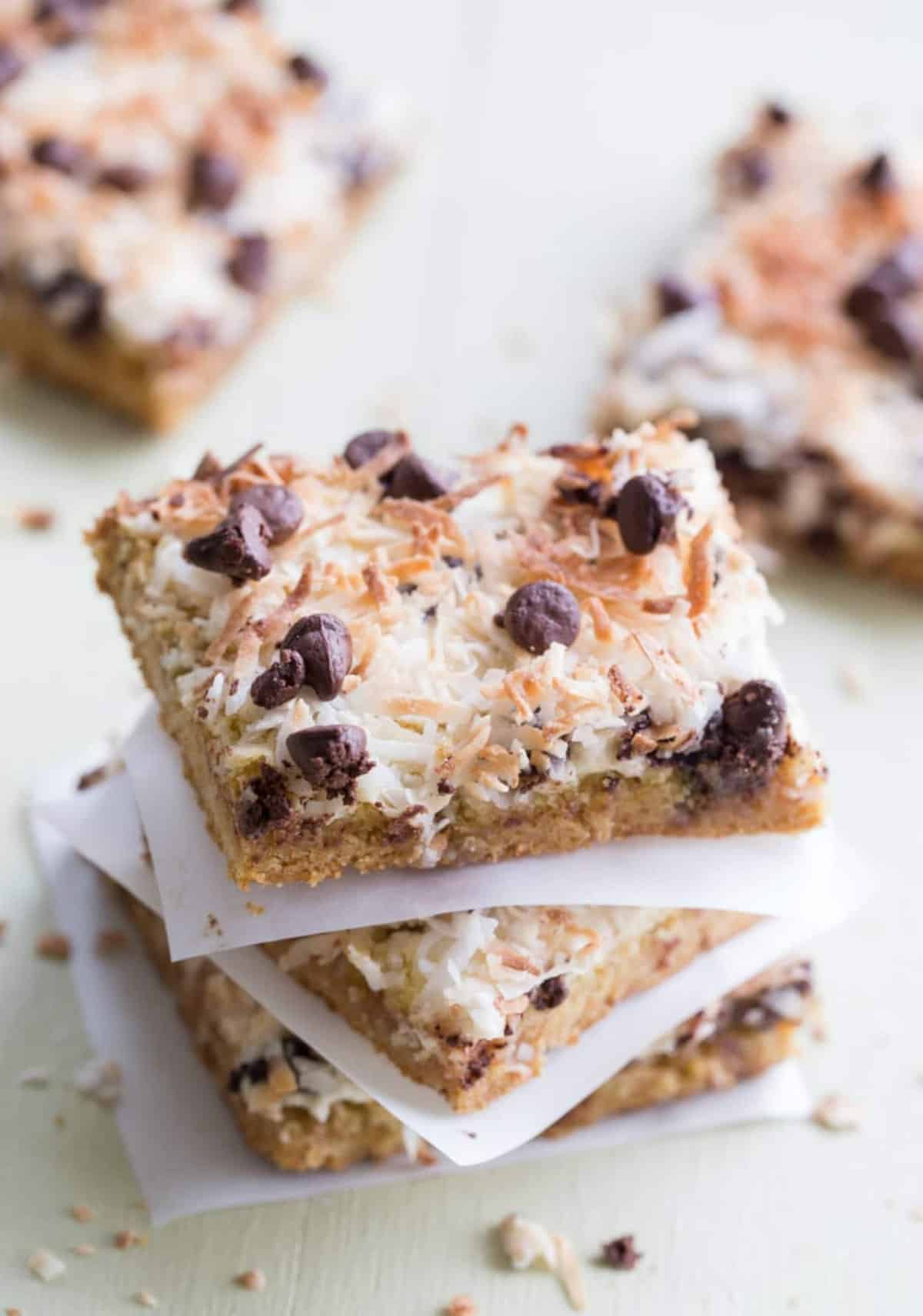Magic cookie bars stacked on top of each other topped with chocolate chip morsels and coconut shavings.