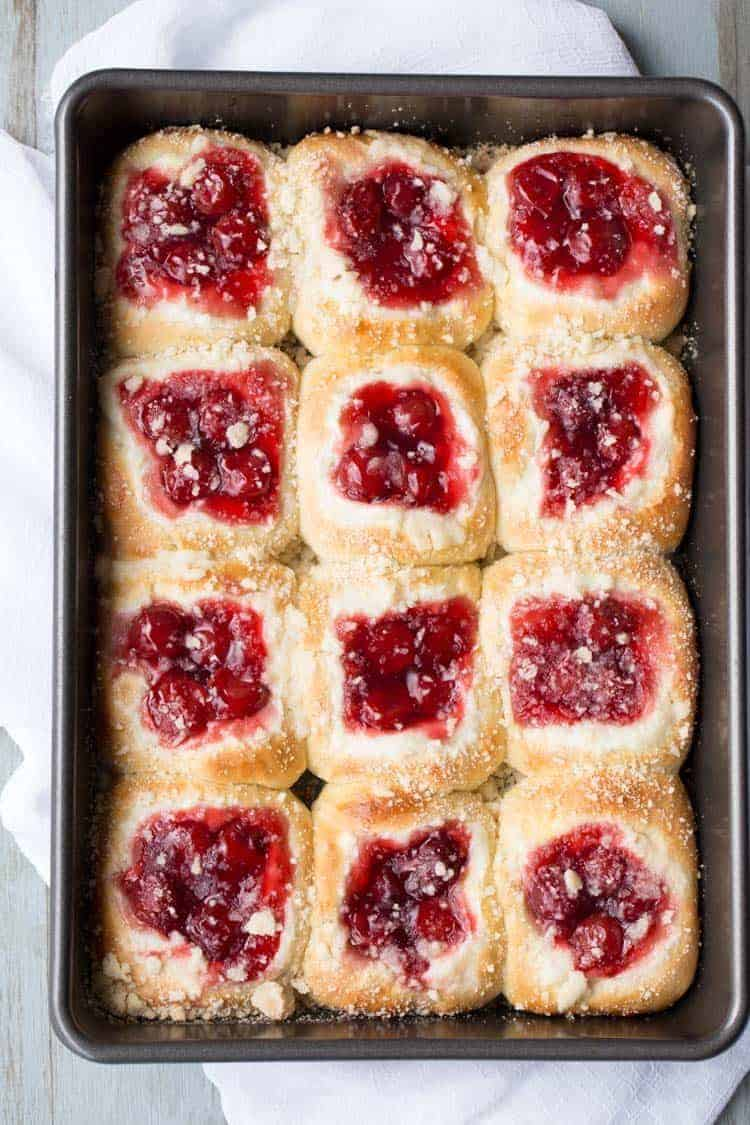 Cheery Cheesecake Buns in a baking sheet topped with a crumb topping.