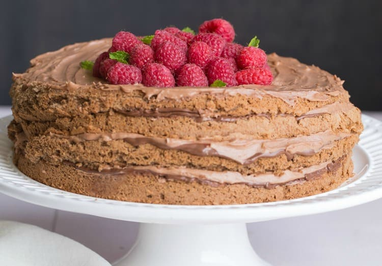 Moise chocolate cake layered with Nutella frosting on a cake stand.