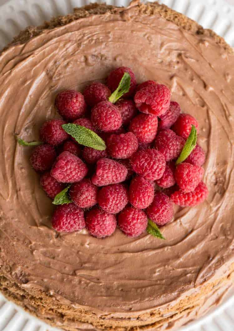 Layered homemade chocolate cake with fresh raspberries and a rich Nutella cream.