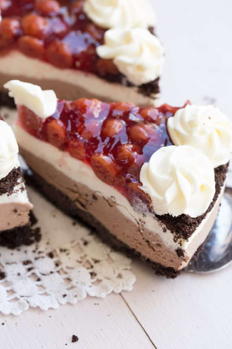 A slice of black forest cherry no bake cheesecake topped with whipped cream.
