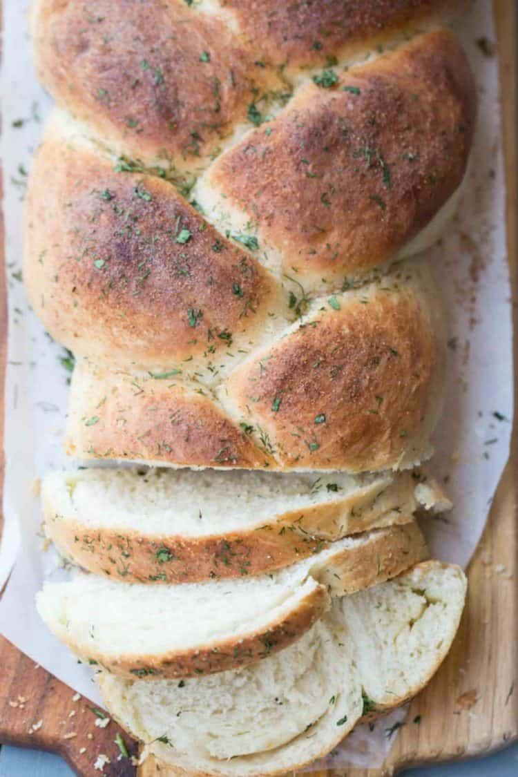 Butter Herb Braided Bread sliced and topped with fresh herbs.