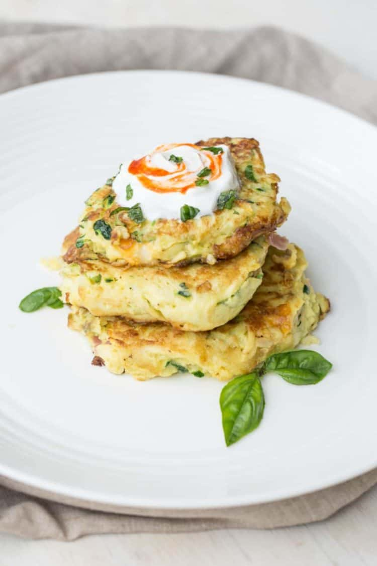 Breakfast zucchini pancakes on a plate topped with sour cream, and basil.
