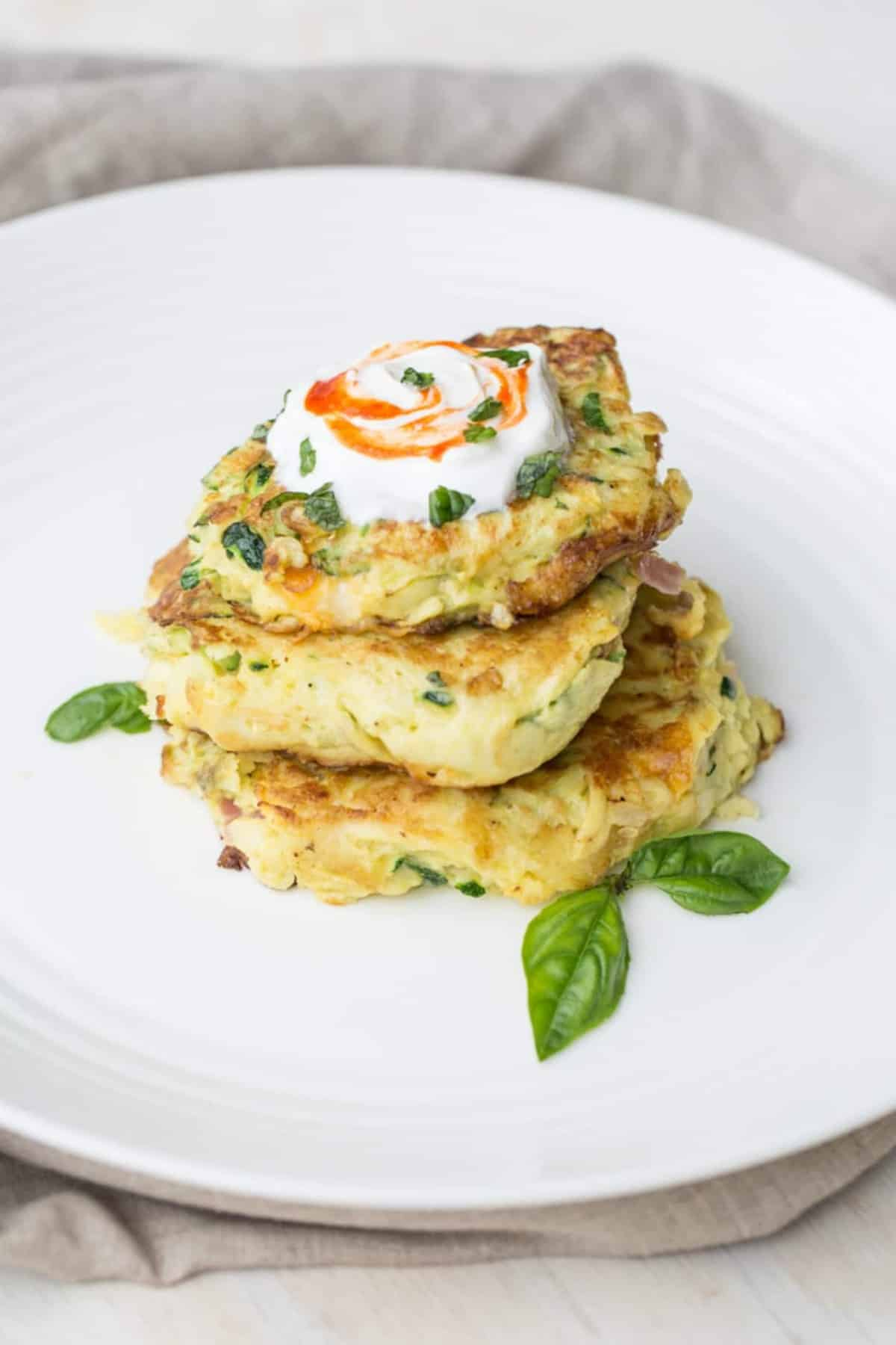 Breakfast zucchini pancakes on a plate topped with sourcream, and basil.