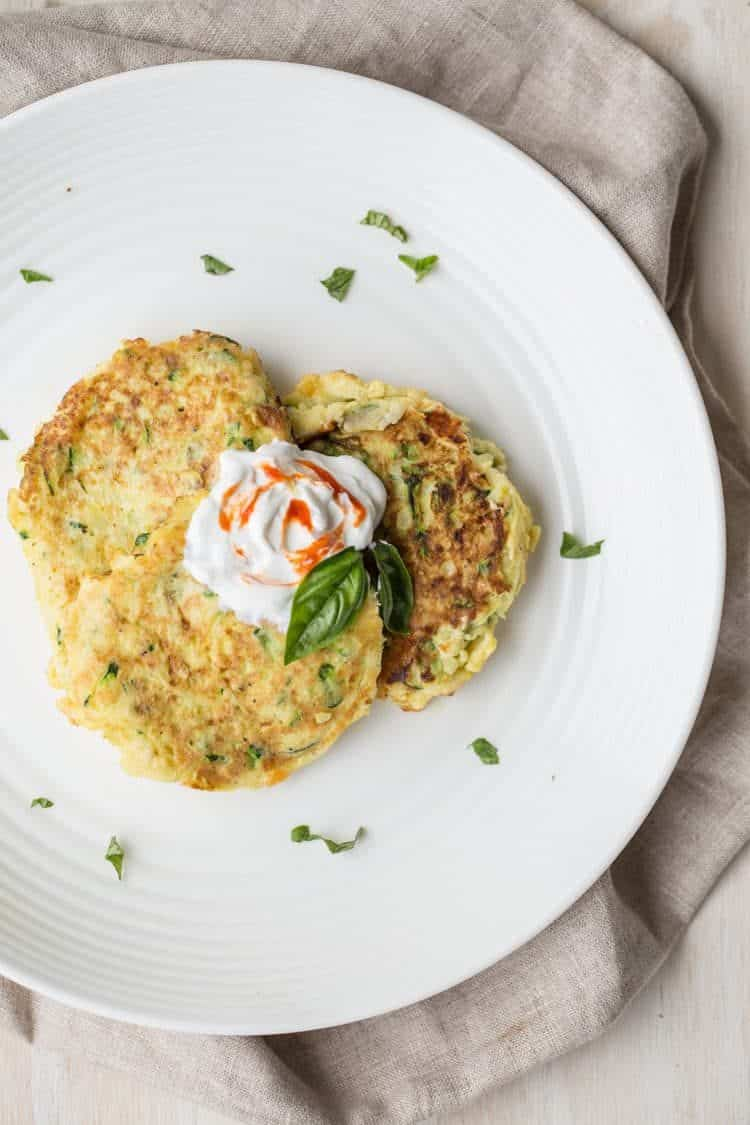 Three zucchini pancakes on a plate with sour cream and sriracha on top with chopped basil.