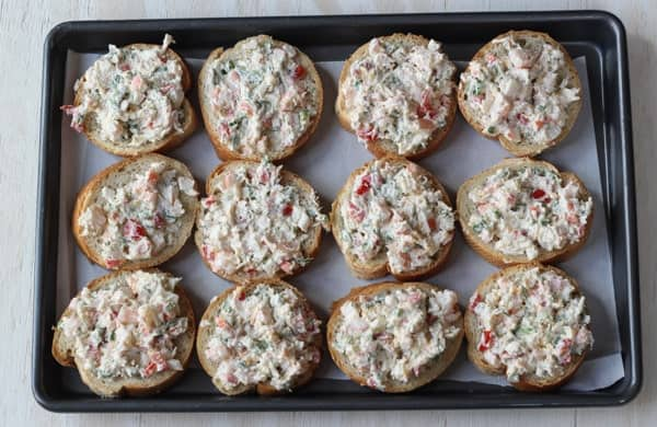 Seafood canapes on a baking sheet ready to bake.