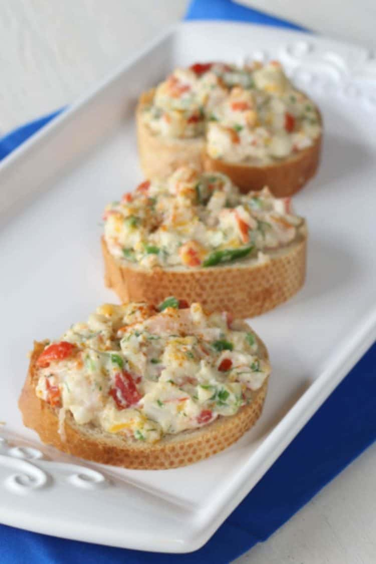 Three hot seafood appetizers on a tray.