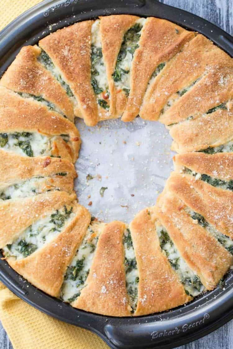 Spinach and Cheese Crescent Ring on a baking sheet topped with Parmesan cheese.