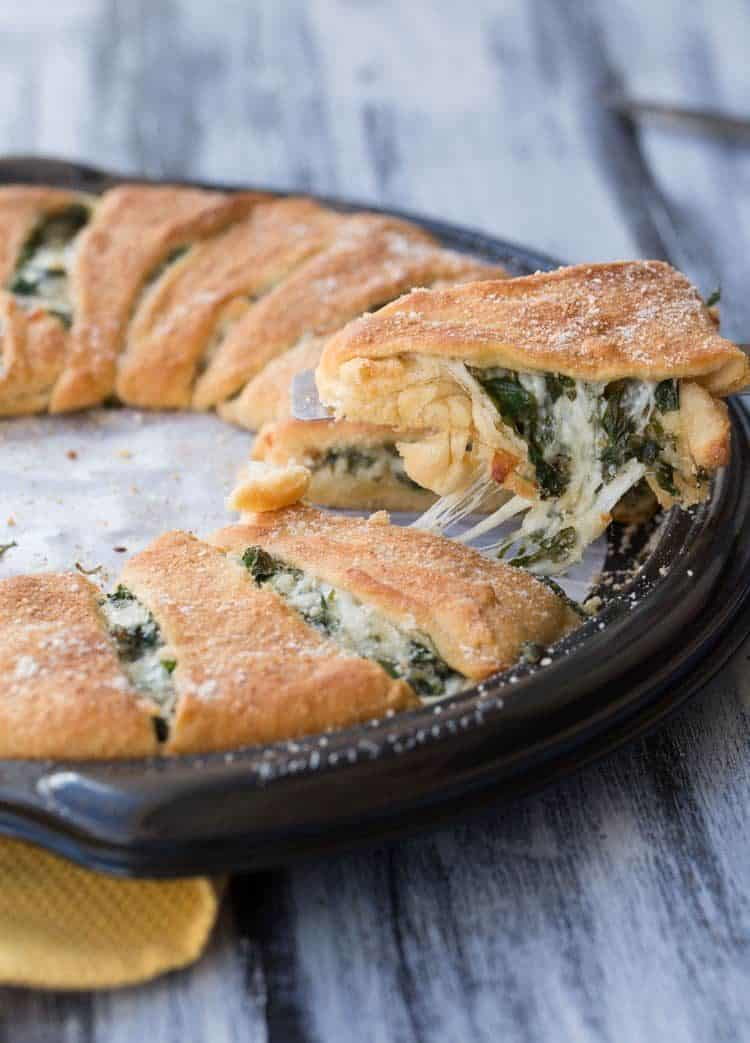 Spinach and Cheese Crescent Ring on a baking sheet, sliced and on a spoon.