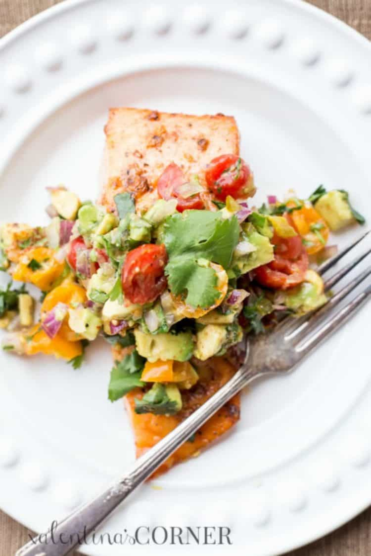 Baked salmon with avocado salsa on a plate with a fork.