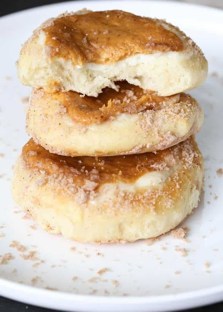 Pumpkin cheesecake buns stacked on top of each other with a sugar crumb topping on a plate.