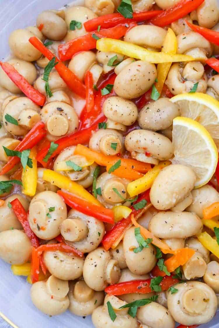 Up close picture or marinated mushrooms with peppers. Topped with ground pepper and lemons.