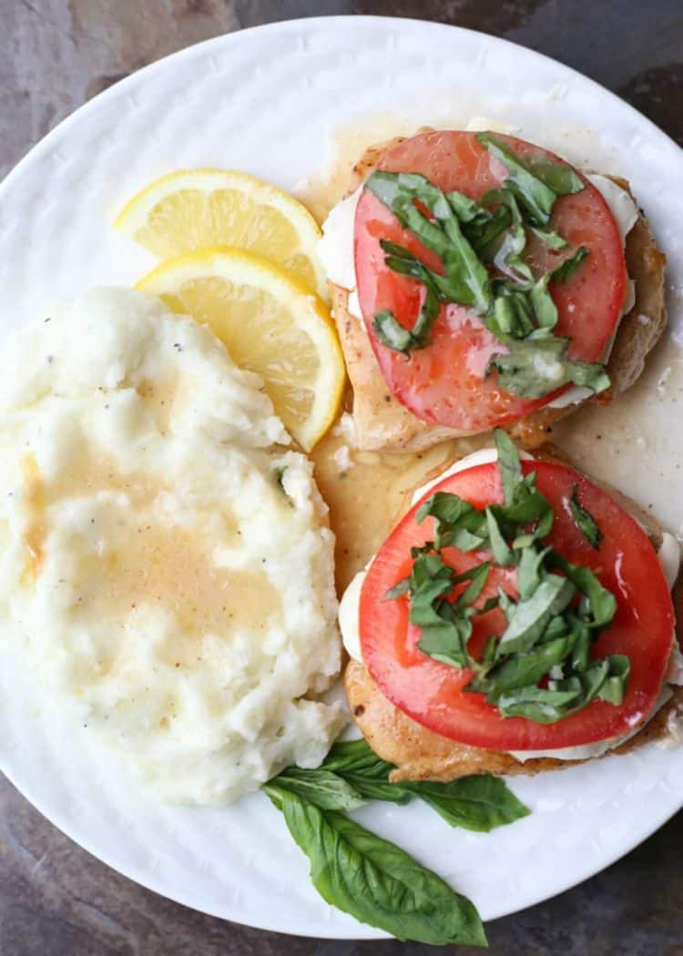Chicken breast topped with tomatoes and basil on plate with mashed potatoes and lemon slices.