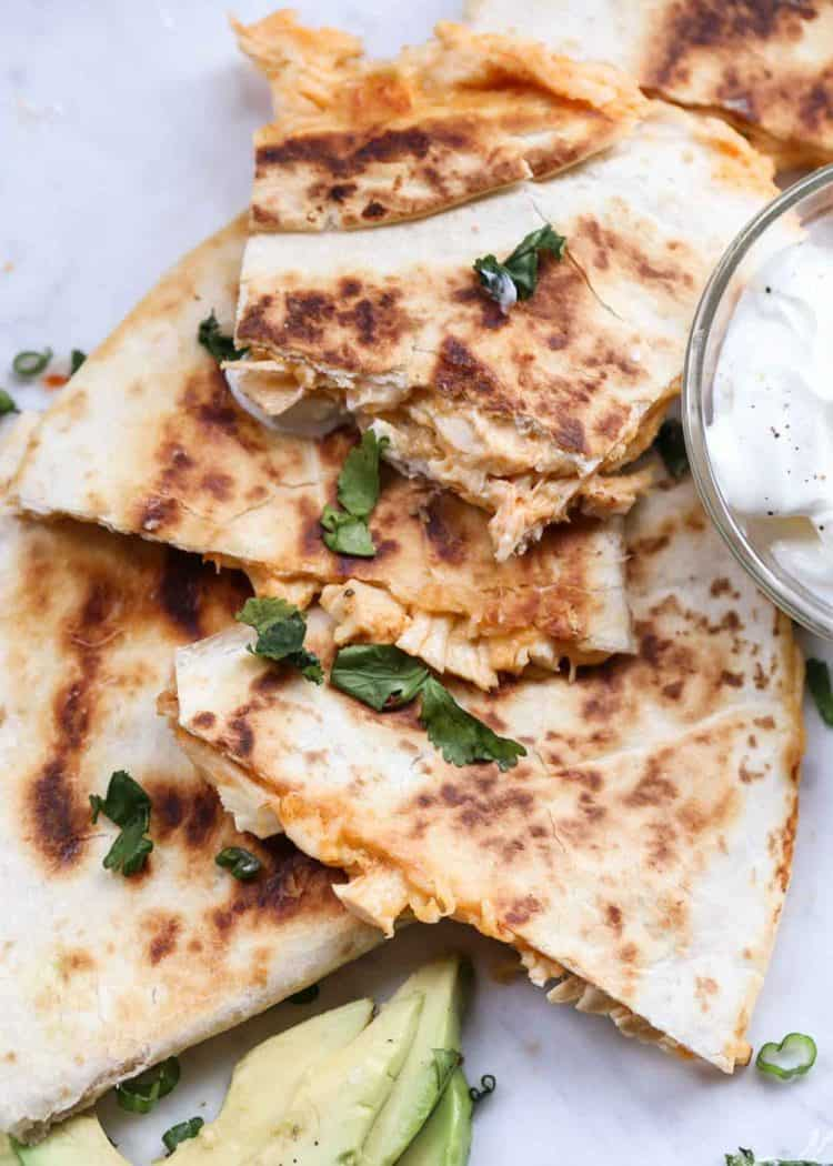Quesadilla piled up next to sour cream, topped with greens.