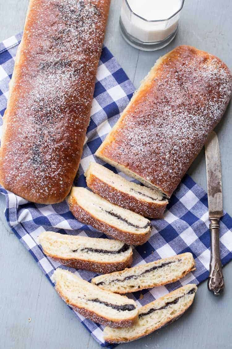 Poppy seed rolls filled with a sweet cream cheese filling, sliced with a cup of milk.