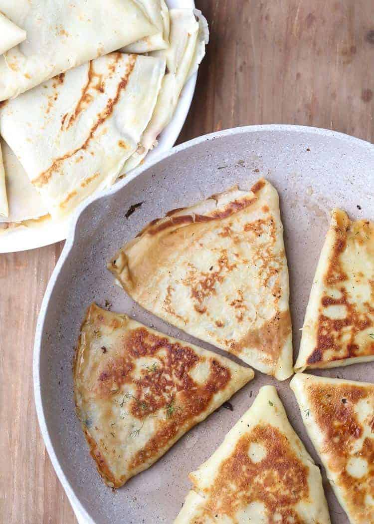 Crepes on a plate, and some in a frying pan.