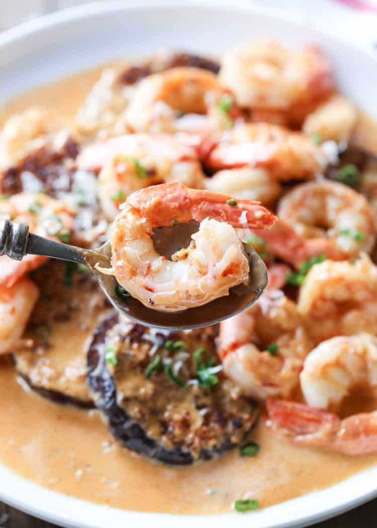 Spicy shrimp on a spoon with fried eggplant and a creamy sauce.
