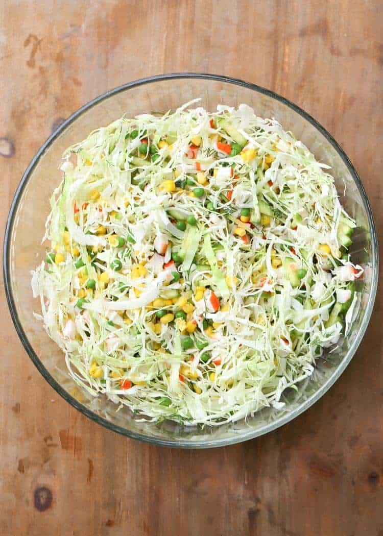Cabbage crab salad in a large bowl with corn.