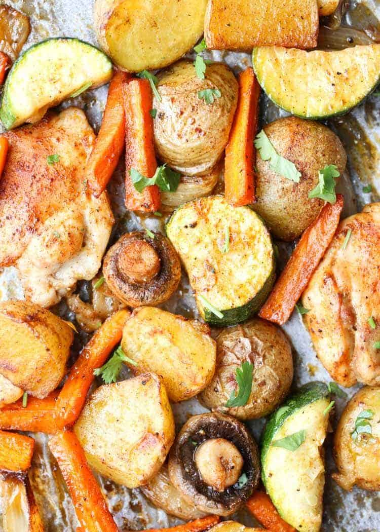 Chicken thighs and potatoes on a baking sheet.