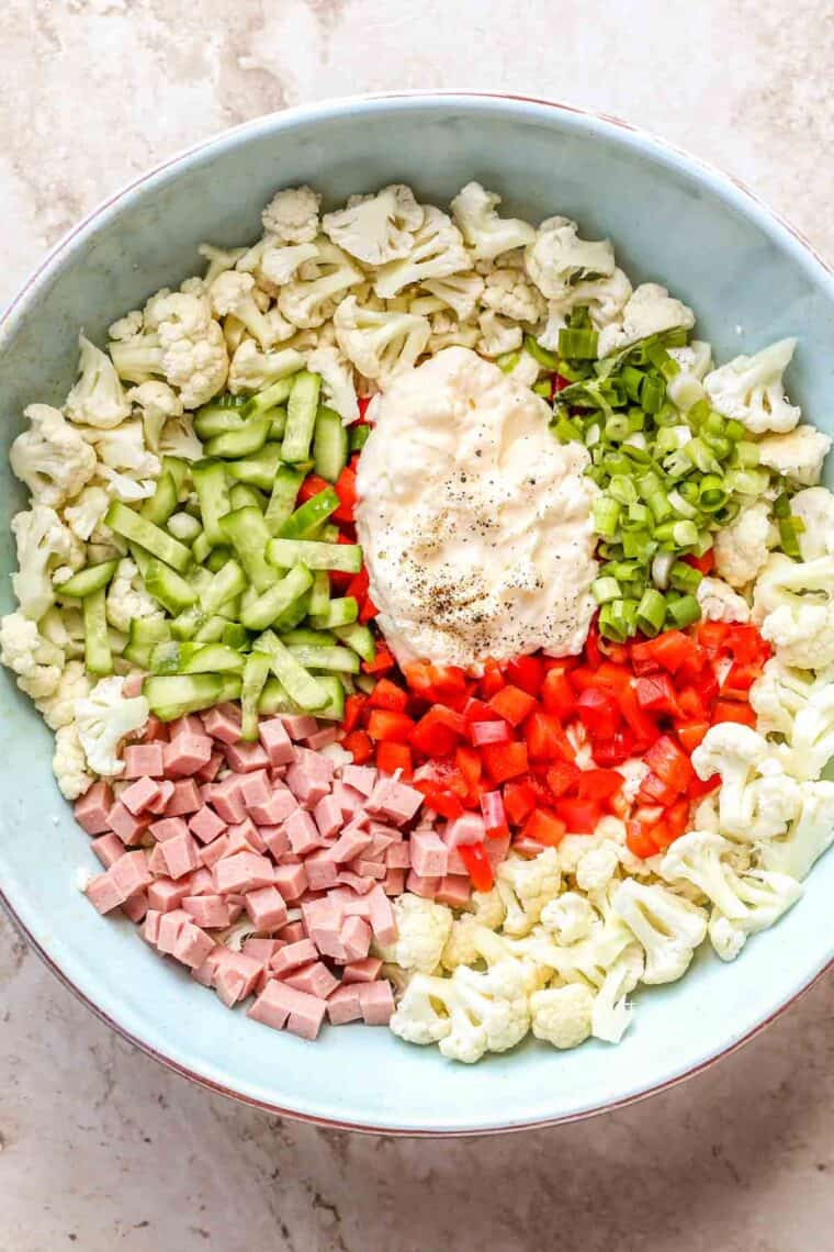 All the ingredients for bologna salad in a blue bowl unmixed.