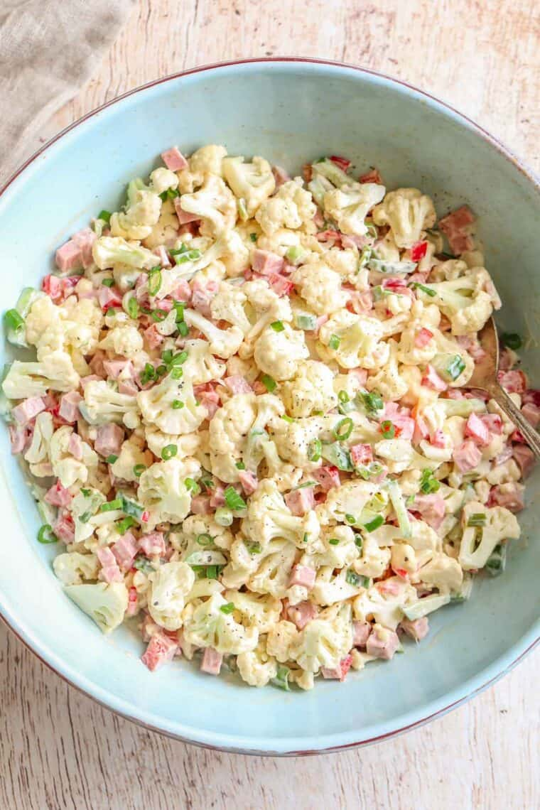 Bologna salad in a blue bowl topped with green onion.