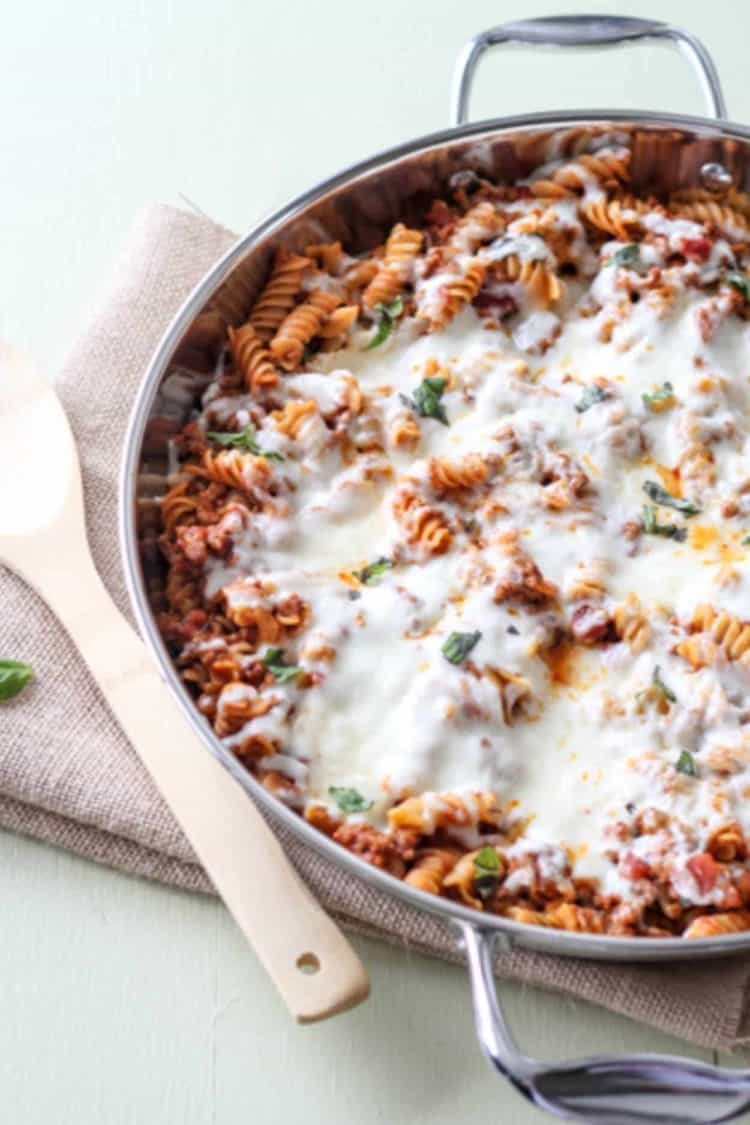 Cheesy meat rotini recipe in a skillet topped with cheese and fresh herbs.