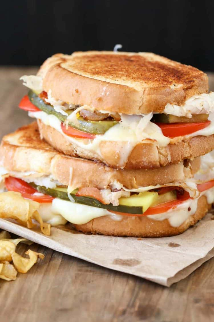 Turkey bacon grilled cheese recipe with two sandwiches stacked on top with chips.