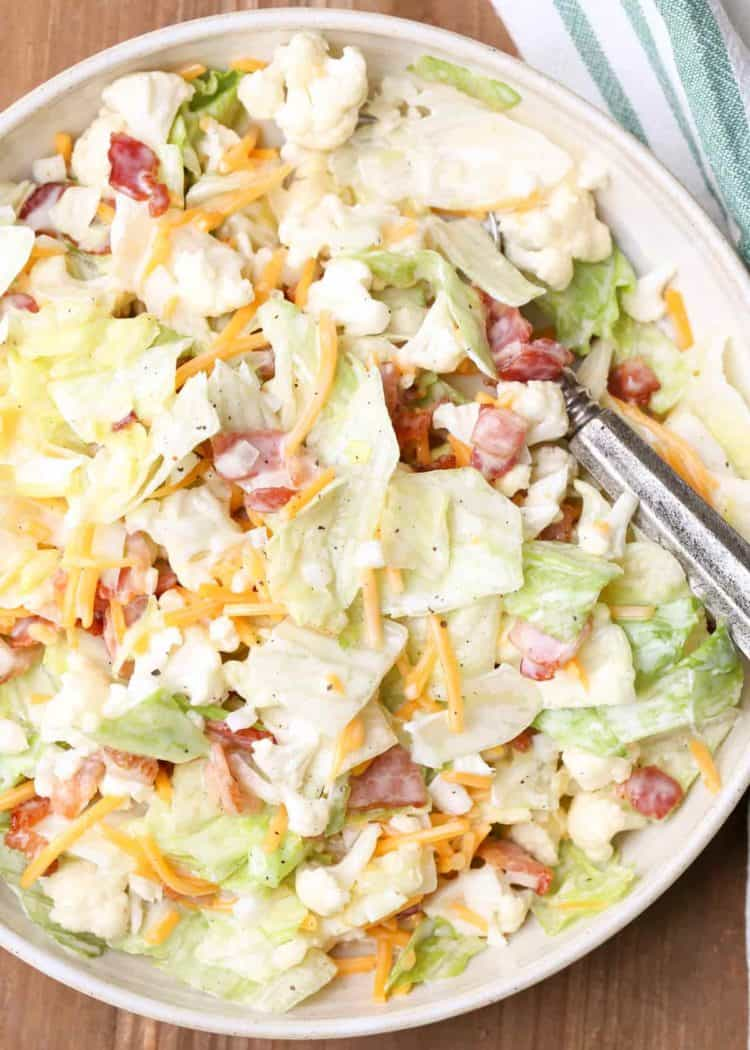 Bacon Cauliflower Salad in a bowl with spoon.
