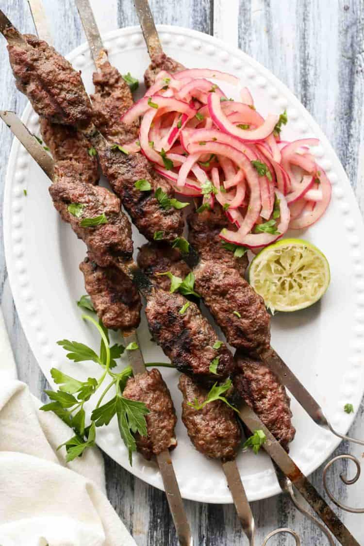 Ground beef kabobs on skewers in a plate with onion salad.