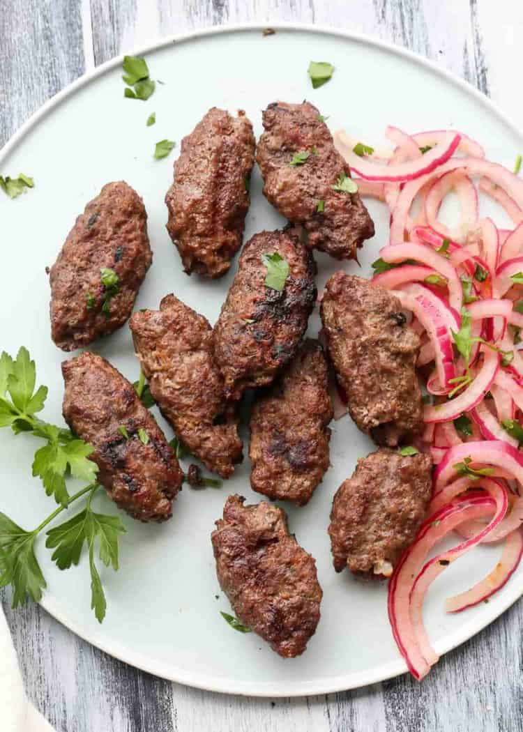 Ground beef kabobs on a plate with onions.