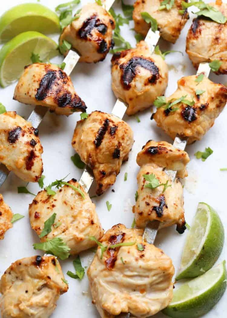 Juicy grilled chicken kebabs with lime on skewers in a plate.