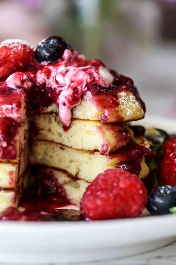 Ricotta pancakes cut into with berry syrup and fresh berries.
