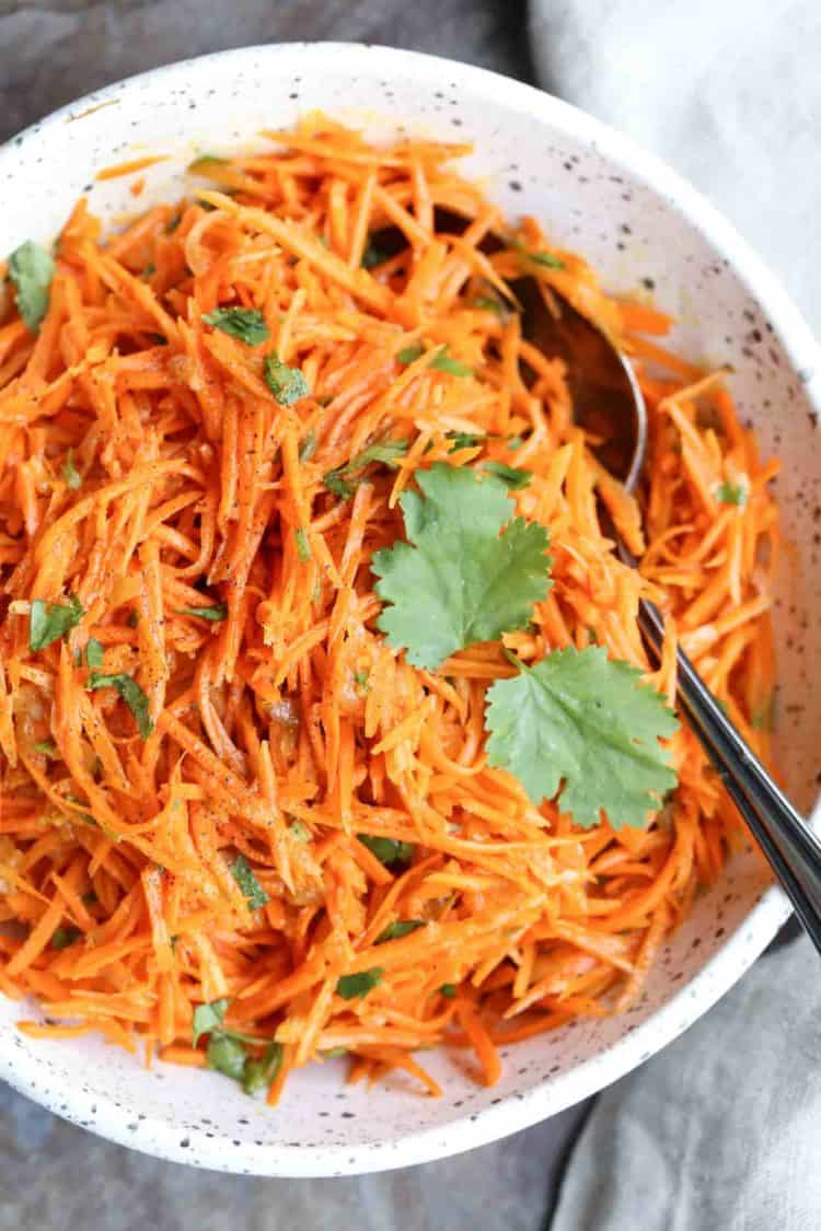 Korean carrot salad recipe in a bowl with fresh herbs topped as garnish.