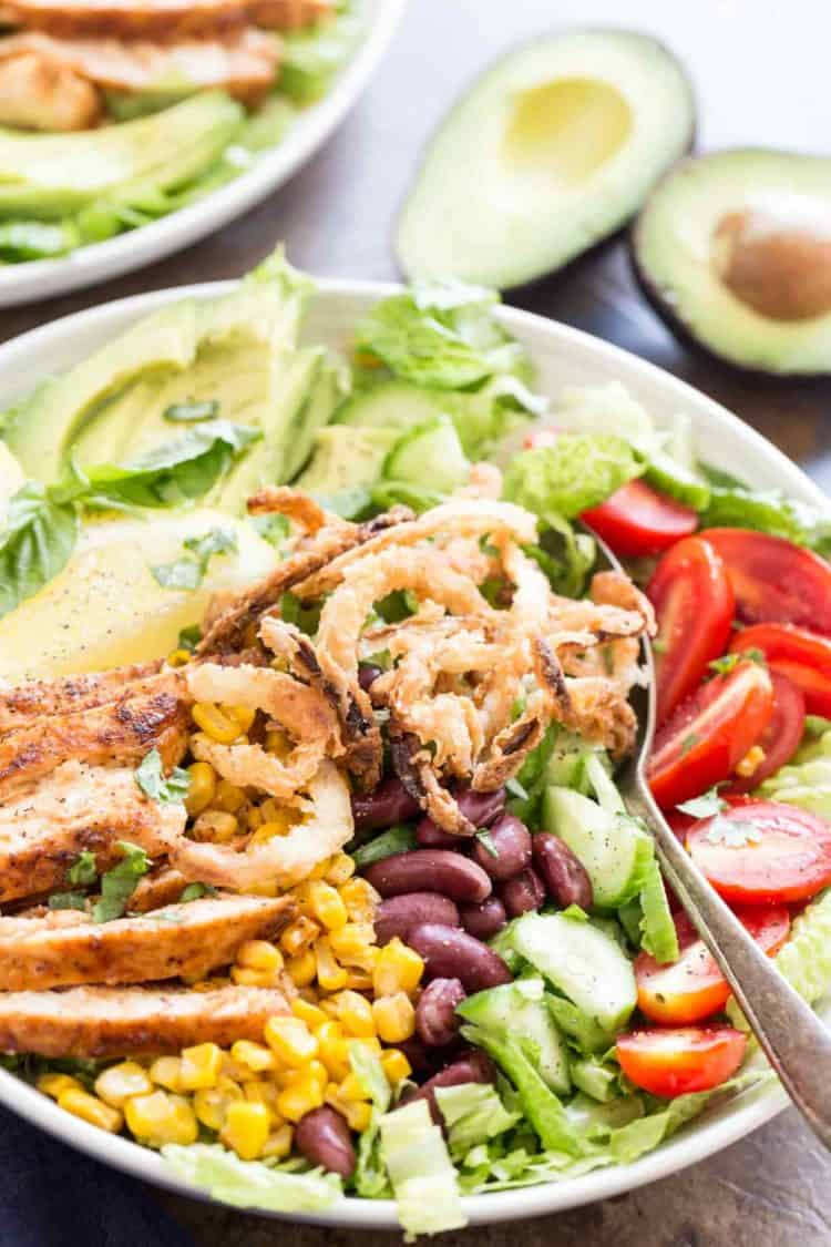 BBQ chicken salad recipe with barbecue chicken, corn, beans, avocado all in a serving bowl with a spoon.