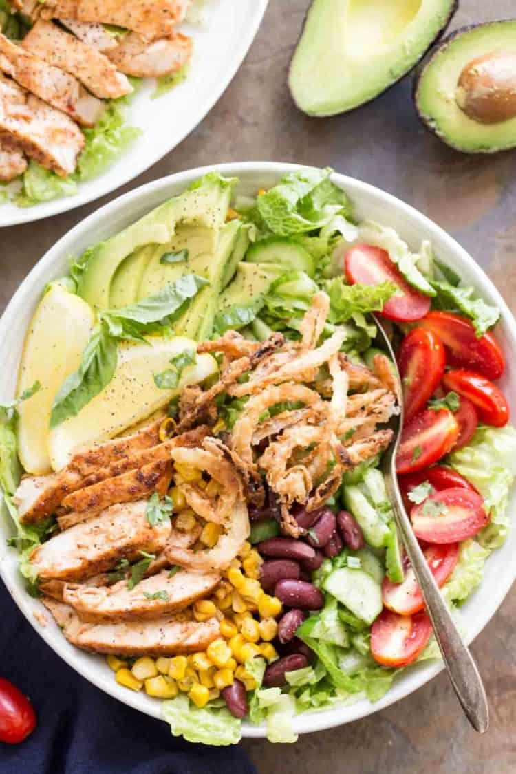 Bbq chicken salad recipe in a bowl with a spoon. Romaine lettuce with chicken, beans, corn, avocado, tomato, onion strings, and cucumbers.