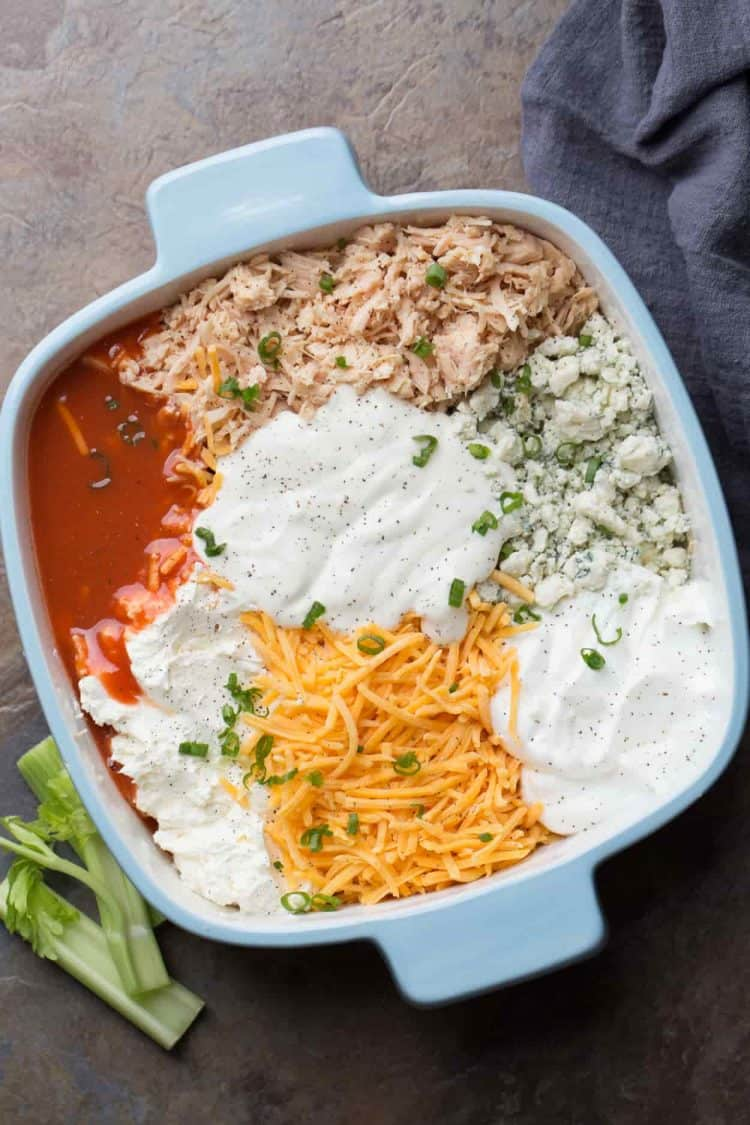 All the ingredients for buffalo chicken dip recipe in a casserole dish.