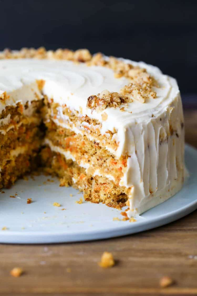 The best carrot cake recipe with on a cake platter with a cream cheese frosting topped with walnuts.