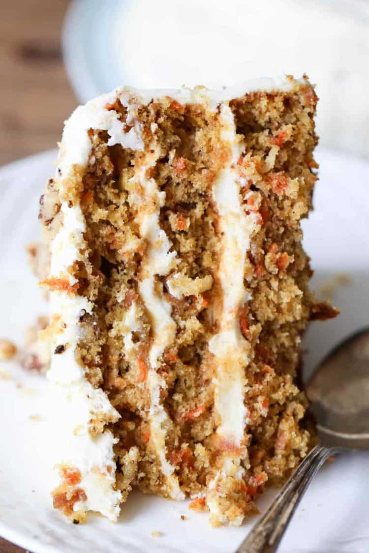 A slice of carrot cake with walnuts, pineapples, and carrots on a plate with a spoon.