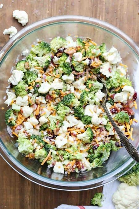 Cauliflower broccoli recipe salad with a homemade dressing in a mixing bowl with a spoon.