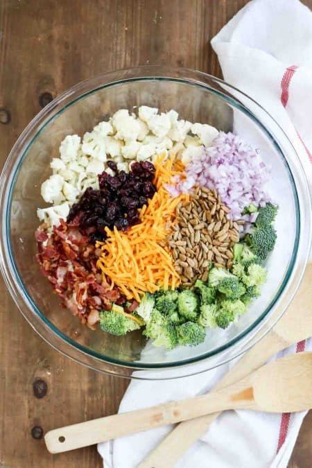 Simple cauliflower broccoli salad recipe in a bowl with cheese, onions, craisins, sunflower seeds, and bacon.