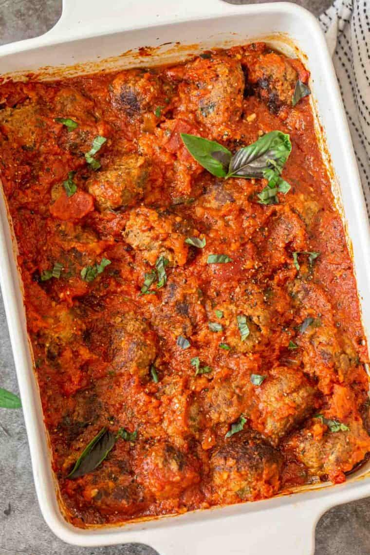 A white casserole loaded with juicy meatballs loaded with marinara sauce topped with fresh chopped basil.