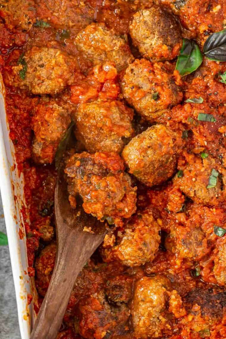 Homemade easy meatballs drenched in marinara sauce topped with fresh basil in a casserole.