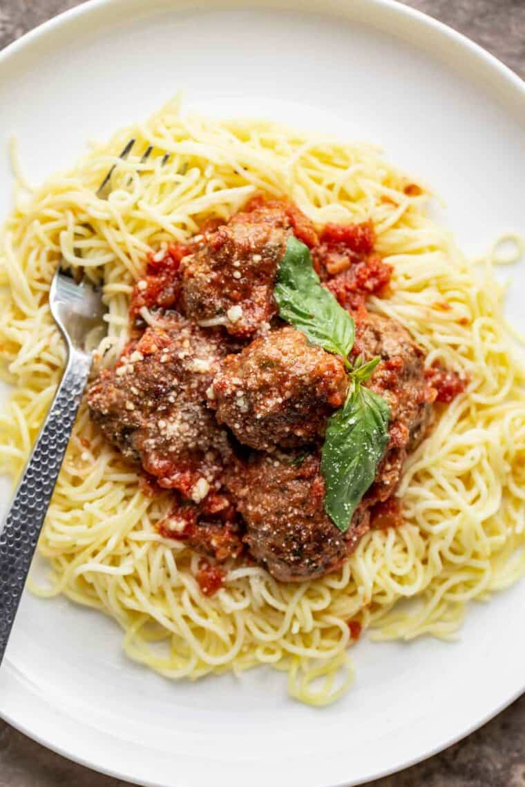 A white plate topped with juicy meatballs over a bed of cooked pasta.
