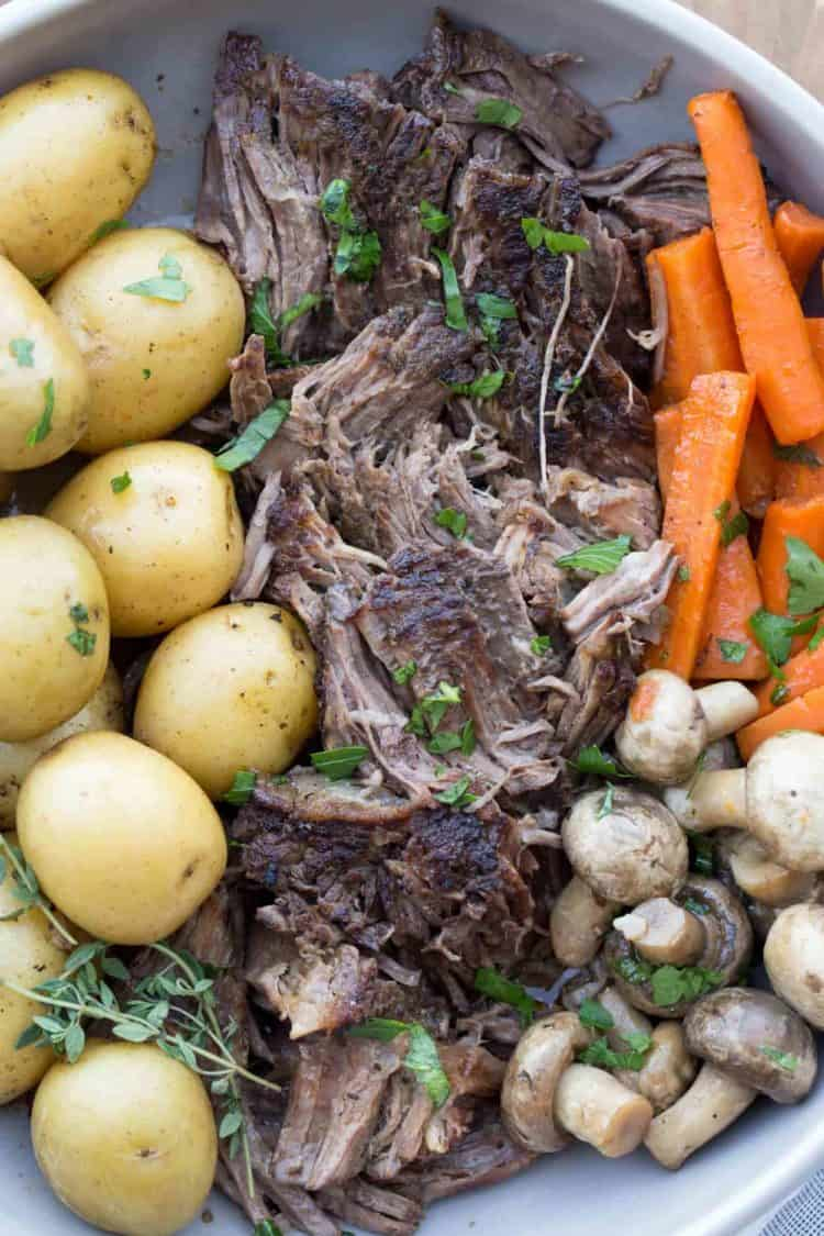 The best slow cooker pot roast recipe in a plate with potatoes, carrots, and mushrooms, garnished with fresh herbs.